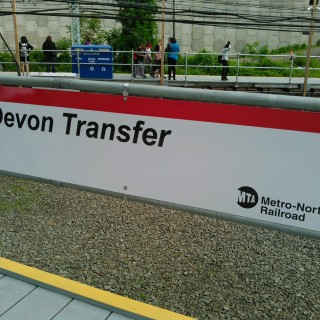 This sign marks the Devon Transfer, a temporary station built along Metro-North's New Haven Line to allow customers to transfer to the Waterbury Branch while repair work takes place on the Devon Bridge. This station is located in the Devon section of Milford, Connecticut, between the Stratford and Milford stations on the New Haven Line. The temporary station opened 4 May 2015; the repair work is expected to take six months.