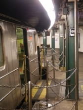 A 1 train waits to return to the uptown track. Notice the gap fillers between the platform and the open train doors.