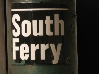 A station identification sign mounted on a cast-iron column.