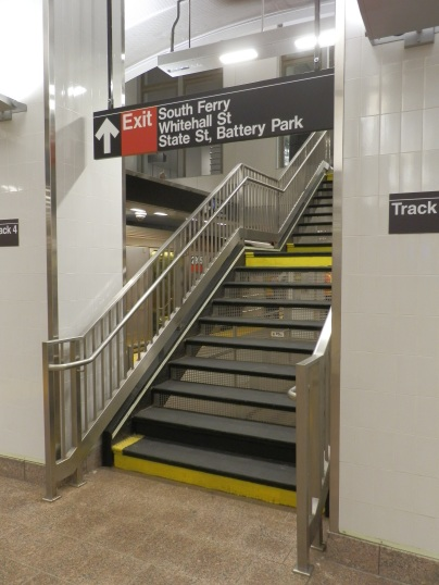 A stairway leads from the platform to a mezzanine at the middle of the station.