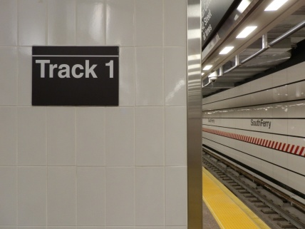Track 1 is the downtown track, while track 4 is the uptown track. (Of course, as the southern terminus of the 1 train, all trains at this station go uptown, regardless of which track they leave from.) There are no tracks 2 and 3 at this station; at Chambers St and further north, tracks 1 and 4 remain the local tracks and are joined by tracks 2 (downtown) and 3 (uptown), which carry express 2 and 3 trains.