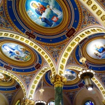 """These Marian murals, a rather astounding 20 in total, are in the rondels over the arcades on either side of the nave. Their historical appearance belies the fact that they are recent additions to St. Joseph's, added during the 2012–14 restoration, as were three other large murals. Each Marian mural represents the Virgin Mary """"as she is revered in different countries,"""" according to a brochure available in the cathedral."""