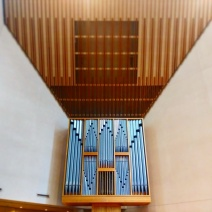 The organ case below the sloped acoustical ceiling in the northwest corner of the sanctuary. Behind the organ case is the corner of Lexington Avenue and East 54th Street.