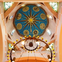 """The dome over the sanctuary. At the center of the dome is the Armenian letter է, signifying what God called himself to Moses, """"I Am"""" or """"He Who Is"""". It is surrounded by symbols of the Christian faith. Below these are eight stained-glass windows depicting the Creation. The dome rests on two intersecting sets of arches — from above they form something like a # — which is characteristic of historic Armenian churches."""