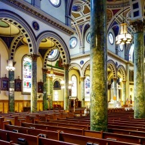 In this view looking across the sanctuary toward the south transept the arcades and Romanesque arches — quite similar to those at the Co-Cathedral of St. Joseph, which was also designed by Francis J. Berlenbach, Jr. — are visible. My suspicion is that the columns are not actually stone but are an imitation called scagliola.