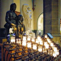 Statues and candles juxtaposed highlight the interplay of light and dark found throughout the church.