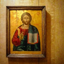 """This icon of Christ is located in the choir passageway at the west end of the arcade, through a doorway to the right of the baptismal font in the previous image. A church brochure explains: """"Jesus wears robes in the style of Byzantine emperors, with the red, an earth color, evoking his humanity, while blue, the heavenly color, symbolizes his divinity. The ornate embroidery of the garment suggests a style characteristic of 16th century Russia. The text Jesus holds in his hands is Matthew 11:28–30. … Notice how Jesus' fingers, held in the position of blessing, form the Greek I C X C abbreviation [for Jesus Christ]."""""""