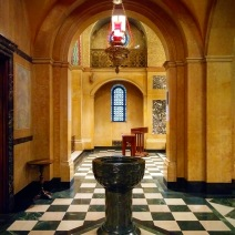 Looking across the baptismal font from the main sanctuary through the arcade to the small side chapel.