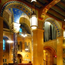 The interplay of mosaic, stone, and light formed by the intersecting arches, vaults, and columns of the adjacent nave, arcade, and chapel is to dazzling effect.